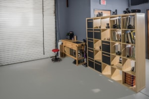 Photo shows MGC photo studio receiving area equipped with a 13' bay door, work bench, storage and library.
