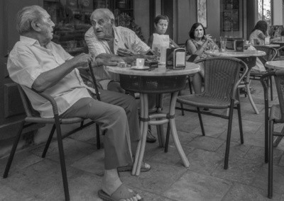 Photo shows two older men sitting at a café being looked at by two women.