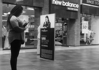 Photo shows a woman looking at her phone while standing in front of a billboard that has a woman on it looking at her phone.