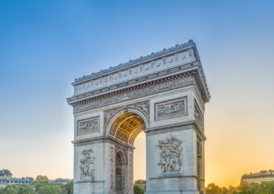 Photo of the Arc D'Triumph with the light of the setting sun streaming through the inside filling it with a warm glow of light balanced against the cool blue sky.