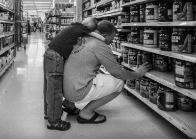 Photo shows a young boy with his arms wrapped around his father who is looking for protein mixes in a department store.