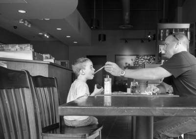Photo of a young boy getting a tase of dads coffee beverage at a local coffee shop.