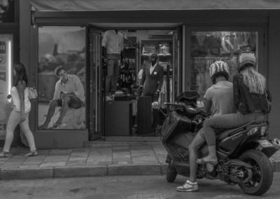 Photo shows a woman walking down the sidewalk as a shoppe mannequin appears to be doing a second take as it leans to see around the doorway. At the same time, a photo of a male model appears to be looking at a guy or girl on a motor scooter that just arrived.
