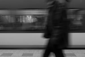 Photo of a person walking past the photographer in one direction blurred while the subway train blurs past the opposite direction