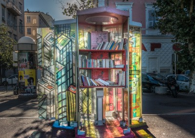 Photo shows an old french telephone booth that has been converted to a book borrow station. Sunlight comes through the hand colored glass that reflects onto the ground.
