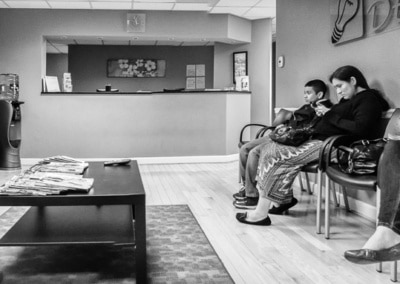 Photo of three people sitting in the dentist office looking at their phones while there is a widescreen TV right in front of them to look at.