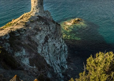 Photo shows a rustic stone tower positioned on a cliff overlooking the mediterranean sea as the sun sets.