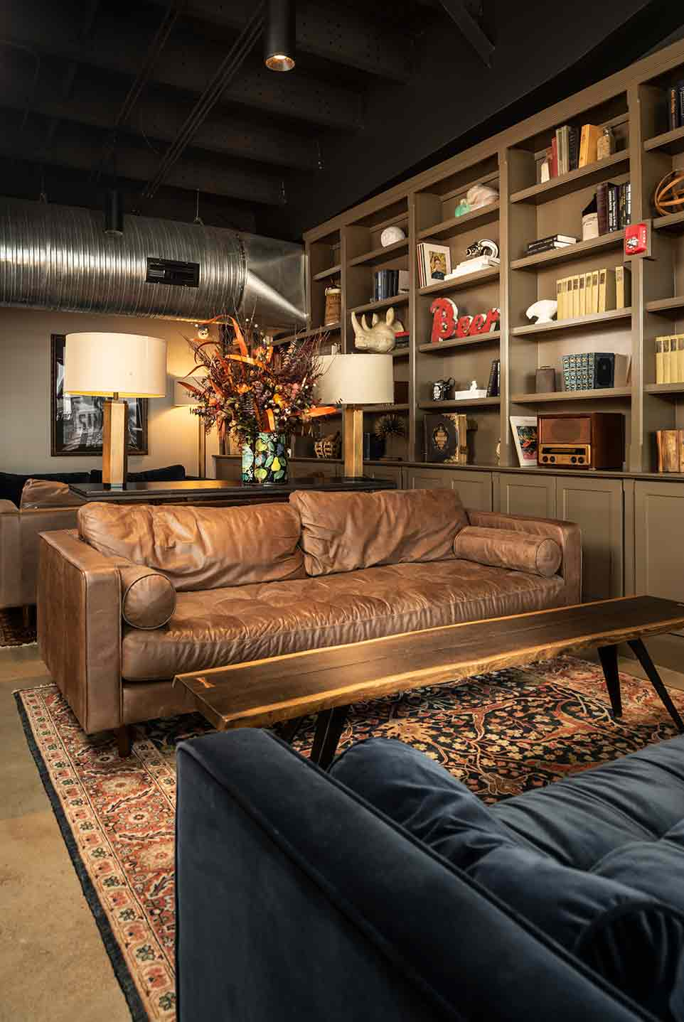 Photo shows an assortment of warm lighting that projects a quite mood amongst the leather seating area and book shelves.