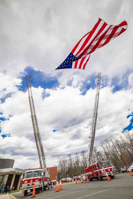 Event photography of two fire trucks flying the U.S. flag at the entryway of the Valor Awards venue.