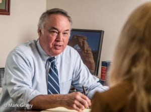 Photo shows an attorney discussing a case with his client in his office.