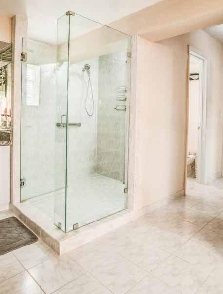 Photo shows a stand up shower with glass door and side.