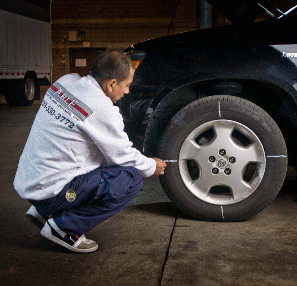 Photo shows a staff member marking the tires of a car that is in long term storage so they can be periodically rotated.