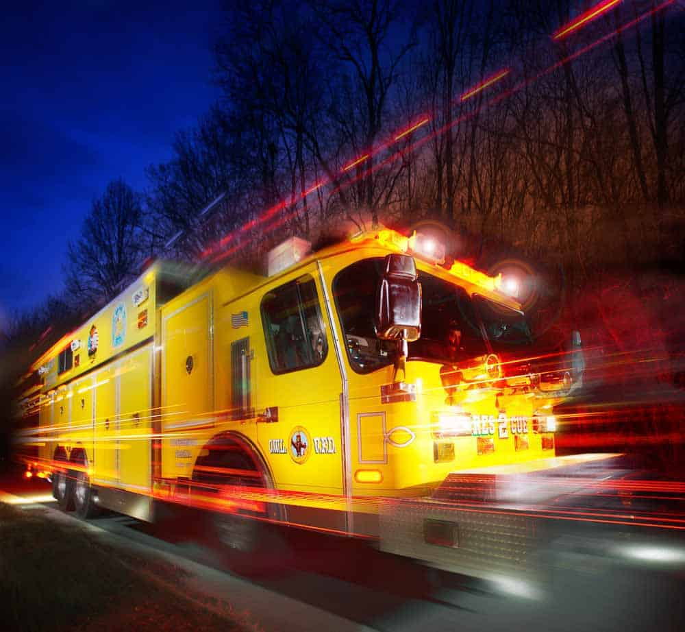 Photo illustration showing the emergency light blazing on a fire truck as it speeds by the camera.