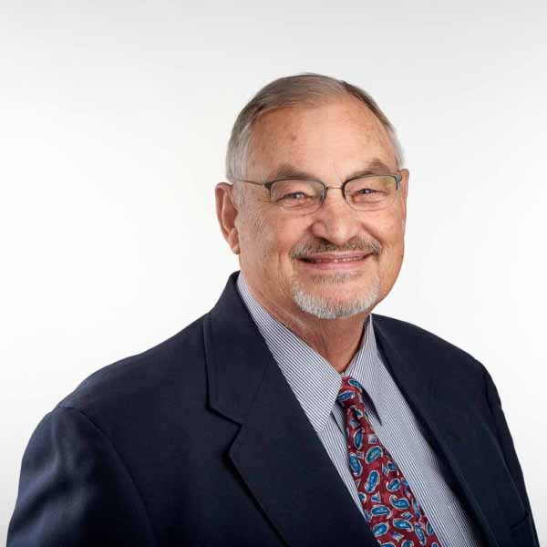 Photo shows a man posing for a headshot for website.
