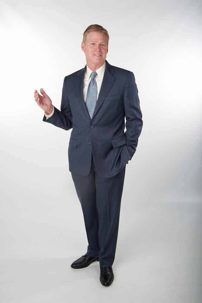 Photo shows a full body view of an executive explaining a service he offers.