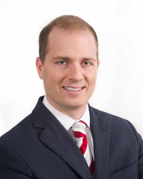 Photo shows an executive posing for a corporate headshot.