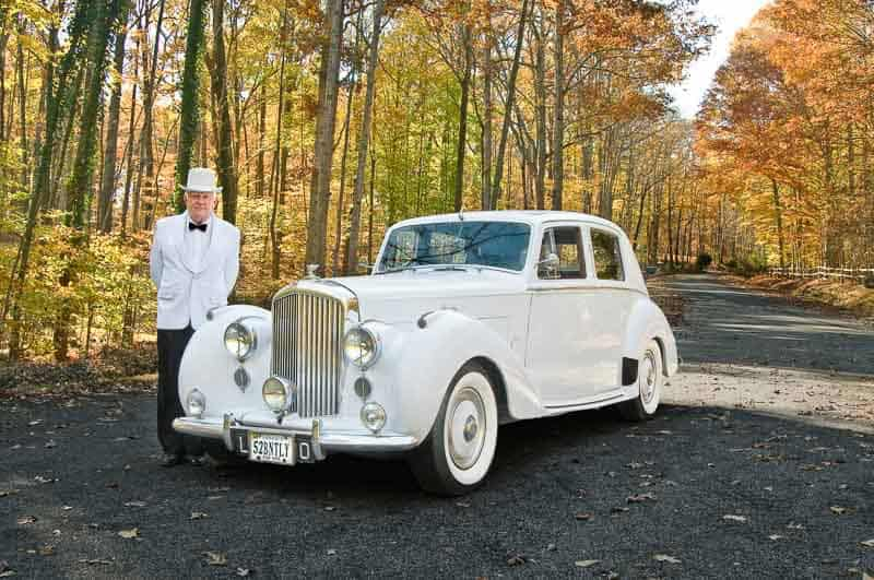 Photo shows the owner of this classic white limousine standing next to it in the fall foliage.