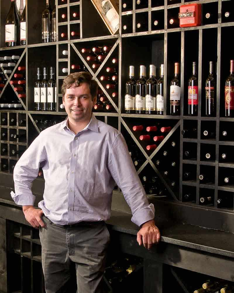 Photo shows a restauranteur posing for an environmental portrait in front of a wall of wine bottles.