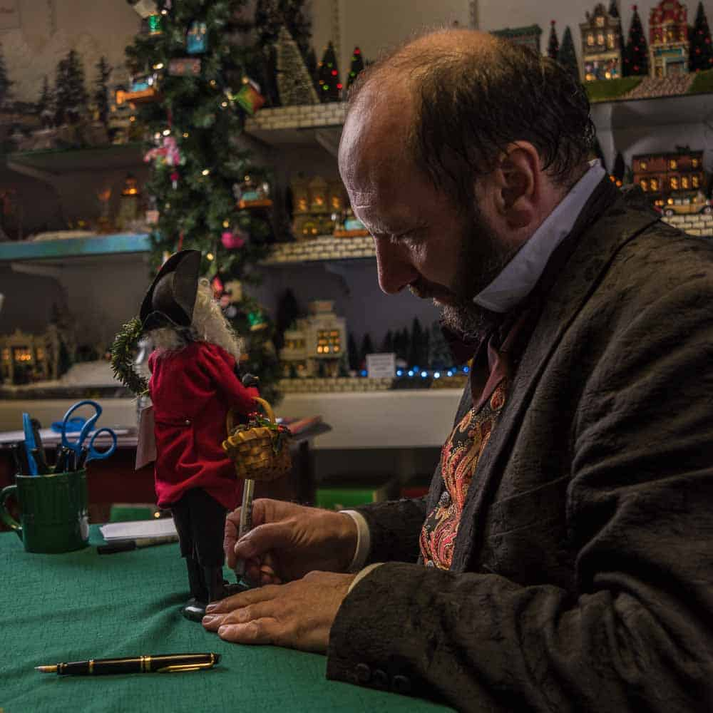 Photo shows the great, great grandson of Charles Dickens autographing a wooden Santa Clause. Photo for Prince William Living magazine.