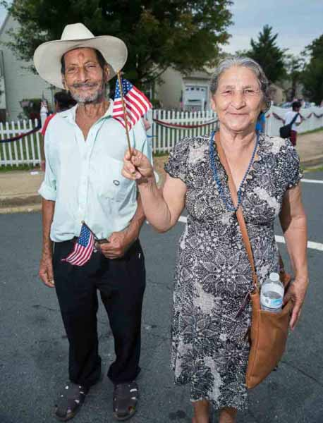 Photo shows an elderly couple from another country waving the American flag during the Dale City 4th of July Parade for Prince William Living magazine.