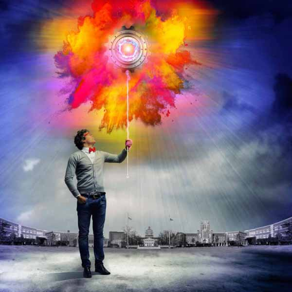 Photo shows a man holding a balloon that looks like a gear that is exploding with color.