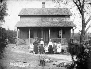 After Photo Restoration of a very old home with a family in front